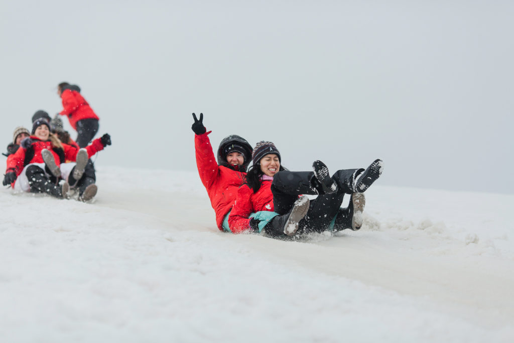 The photo shows a snowy slope with a white sky behind. People are sliding down the slope on their bottoms. They all wear the red Homeward Bound Jacket.