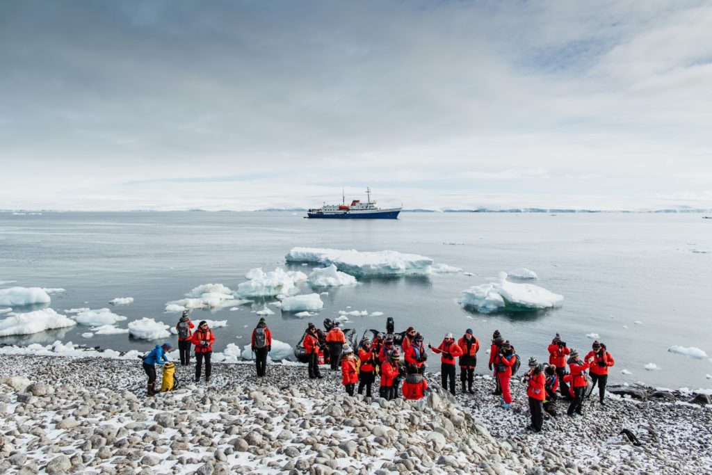 A wide-angle photograph showing participants of homeward bound in their red jackets awaiting briefing on the rocky snow-covered shore. Small ice bergs can be seen in the water near the shore. The ship Ushuaia is in the middle ground. The horizon shows a large ice shelf. The scene is bright and sunny.