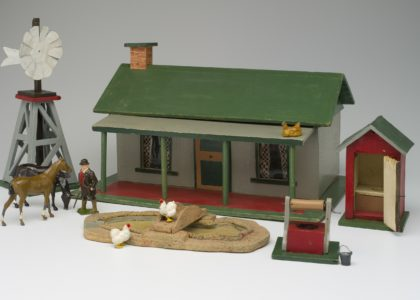 Wooden toy farm house, windmill, wishing well, duck pond and outside toilet with lead farm animals and farmer.