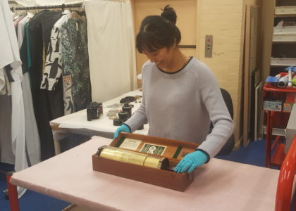 Examining a slide rule for collection documentation in the museum store