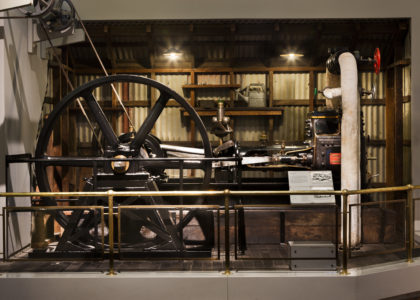 A steam engine with a large flywheel on display in the Powerhouse Museum