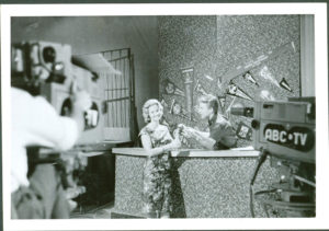 Photograph, showing ABC television studios, paper, photographed by Bob Eaton, printed by Kodak, Sydney, New South Wales, Australia, 1959-1961 Black and white landscape-format photographic print with white border. The photograph features Johnny O'Keefe conversing with a woman on set at ABC's Gore Hill television studios. The text 'Six O'Clock Rock' is handwritten in lead pencil on the reverse side of the image.