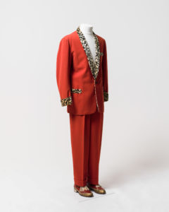 Mens suit consisting of jacket and trousers, worn by Johnny O'Keefe. -1 Jacket made of red fabric with black and cream coloured 'leopard print' velvet trimming at collar, cuffs and pockets. The jacket has a shawl collar with the collar and lapels lined with leopard print velvet which extends on the inside of the jacket to the waist. The jacket fastens at the waist with a single black plastic button which is sewn to the jacket with red cotton. The jacket is long sleeved and the cuffs are trimmed with leopard print velvet. The jacket has a fake external left breast pocket and two fake external waist pockets on the left and right sides, all pockets are trimmed with leopard print velvet. There are no internal pockets. The inside of the jacket is lined with a red [silk] fabric and leopard print velvet lines the collar and lapel area extending to the waist. The shoulders are slightly padded. The jacket has several moth holes including two on the back of the right shoulder and two below the button. The lining has a hole at the neck and is torn at each armhole and has detatched from the velvet below the buttonhole. The velvet lining is worn around the neck and above the button. -2 Trousers made of red fabric, matching trousers to jacket (98/32/2-1). Trousers have 2 side pockets and a coin pocket at the waist on the right side. Inside of pockets are made of a cream cotton fabric. Trousers are pleated at the waist at the front and back and have 4 wide belt loops formed in the pleats and one thin belt loop and the centre back of the waist which has a safety pin attached. Trousers fasten at the centre front with a metal zipper, a metal hook and eye and an internal button on the left side of the waist which fastens to a buttonhole on a triangular extension of red fabric on the right side. The trousers are unlined except for the inside waistband which is lined with a band of cream ribbed silk and the zipper which is lined with black [silk] fabric. The trousers are hemmed to give the appearence of turned up cuffs at the hem of each leg. The fabric forming the inside of the right pocket has a handwritten inscription in black ink, 'O'Keefe's [sic]/3483'. There are white marks on the legs and repairs have been made to the crotch area.