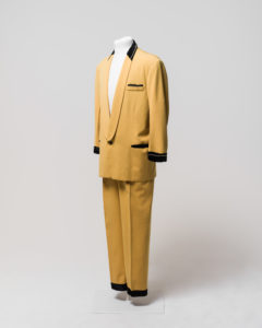 "Men's suit consisting of jacket and trousers, worn by Johnny O'Keefe. -1 Jacket made of yellow [cotton] fabric with black velvet trimming at collar, cuffs and pockets. The jacket has a shawl collar with the neck area trimmed with black velvet decorated with a string of diamantes around the neck. The lapels are of the same yellow fabric and extend to the single button fastening at the waist. The button is made of brownish-black plastic. The jacket is long sleeved and the cuffs are trimmed with black velvet decorated with a string of diamantes around the front half of both cuffs, some diamantes are missing from both cuffs. The jacket has a fake external left breast pocket trimmed with black velvet and diamantes, one diamante appears to be missing from the end of the string. The jacket also has two fake external waist pockets on the left and right sides which are trimmed with black velvet. The jacket is lined with salmon pink silk and has no internal pockets, the shoulders have some padding. A maker's label is sewn inside the jacket at the left breast, the label is cream coloured with black embroidered text ""Len Taylor/Sydney/American Clothes Stylist"". The label is partly detached from the jacket. The jacket has black marks exteding horizontally from just above the right waist pocket and discolouration in the lining at the centre back neck area and in various places on the external yellow fabric. There are several moth holes in the lining and in the external fabric particularly just below the right waist pocket. -2 Trousers made of yellow [cotton] fabric, matching trousers to jacket (98/32/1-1). Trousers have 2 side pockets and are pleated at the front of waist. Trousers fasten at centre front with a metal zipper, metal hook and eye and internal button which fastens to button hole on a triangular extension of yellow fabric (this internal button is missing). There are seven belt loops around waist for a thin belt. Trousers are unlined except for the inside waist which is lined with a band of ribbed cream silk, covering a rougher piece of hessian coloured fabric, the zipper is also lined with cream silk. The waistband lining is partially detached from the trousers. The legs of the trousers are hemmed with black velvet giving the appearence of a cuff at the hem of each leg. The cream cotton fabric forming the inside of the left pocket has a handwritten inscription in black ink ""J.R O'Keef"" [sic] and the fabric forming the inside right pocket has a handwritten inscription in black ink ""FHC""."