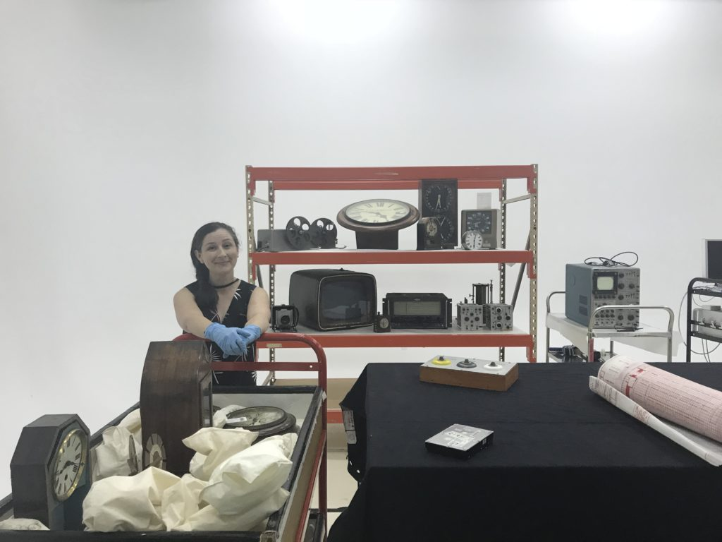 Collections Officer Sarah Heenan brings a trolley-load of objects up from the collection store.