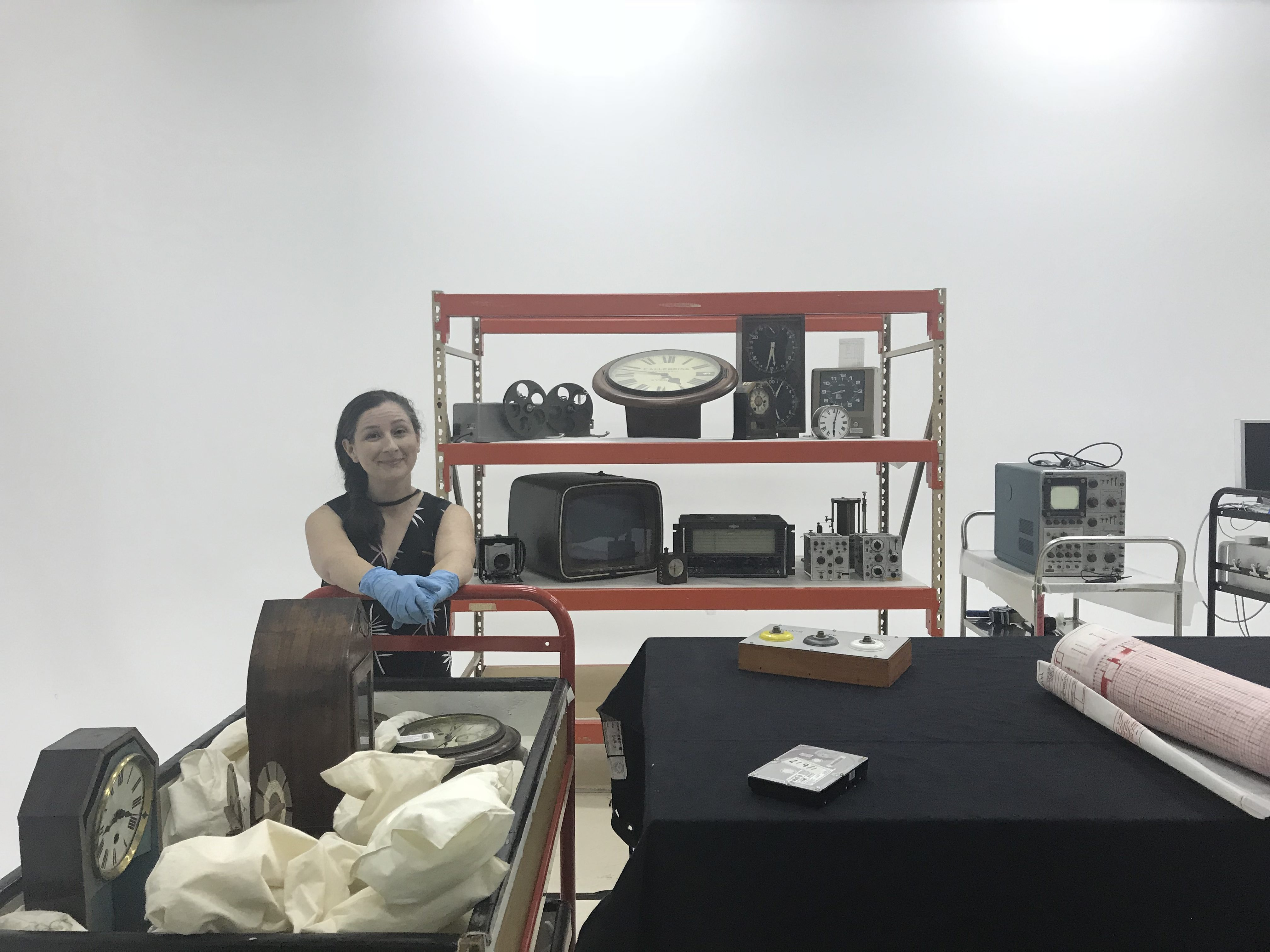 A woman in a black top poses with a trolley full of collection objects. The objects are packed with cushions and small bean bags. The woman is wearing blue latex gloves. Behind her is a set of industrial shelves containing more Museum objects.
