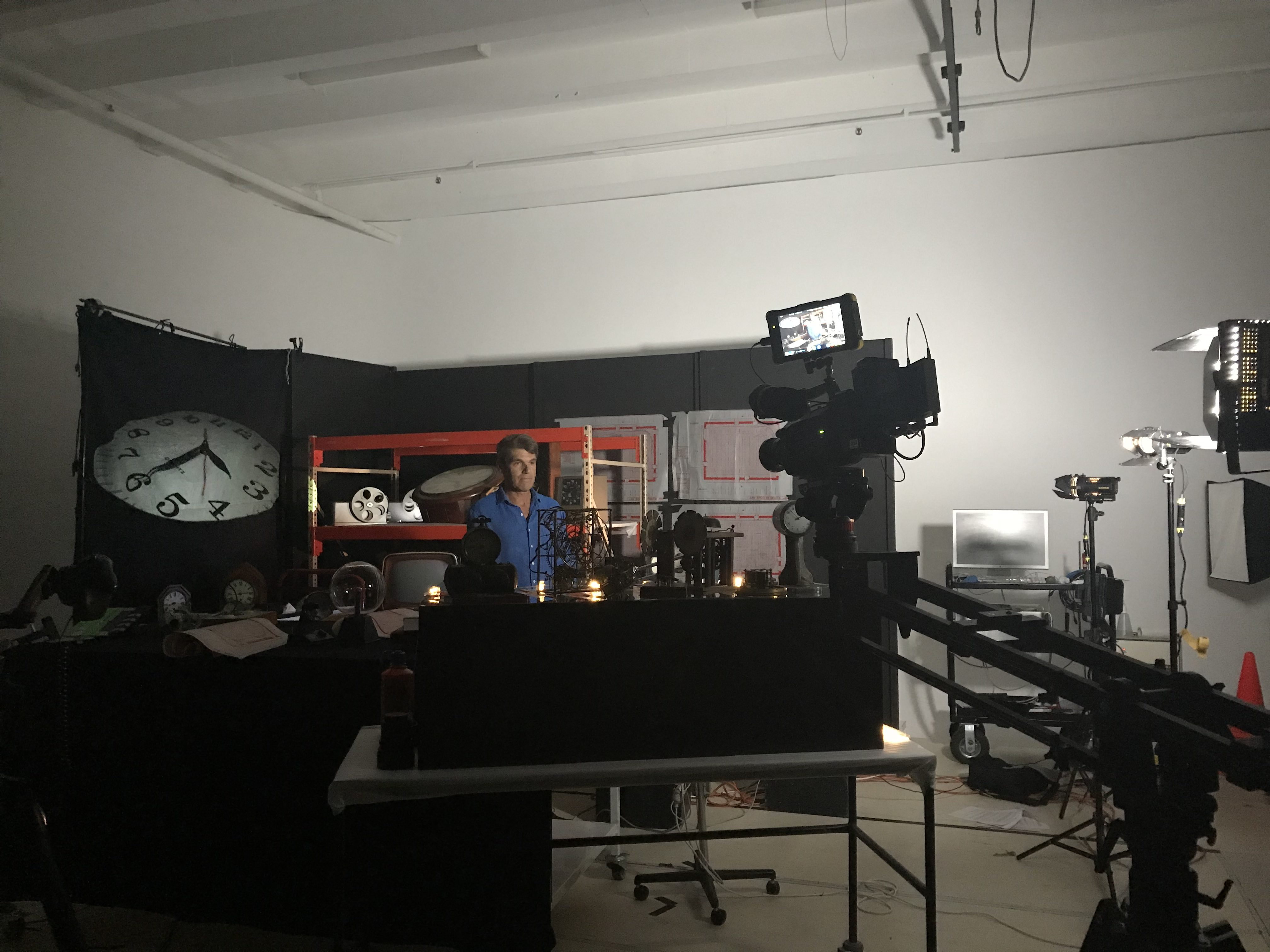 A man in a blue shirt during filming. In the foreground is a plinth of clocks and sciency objects. In the background is a set of industrial shelving with more Museum objects. A TV camera can be seen at the edge of the photo.
