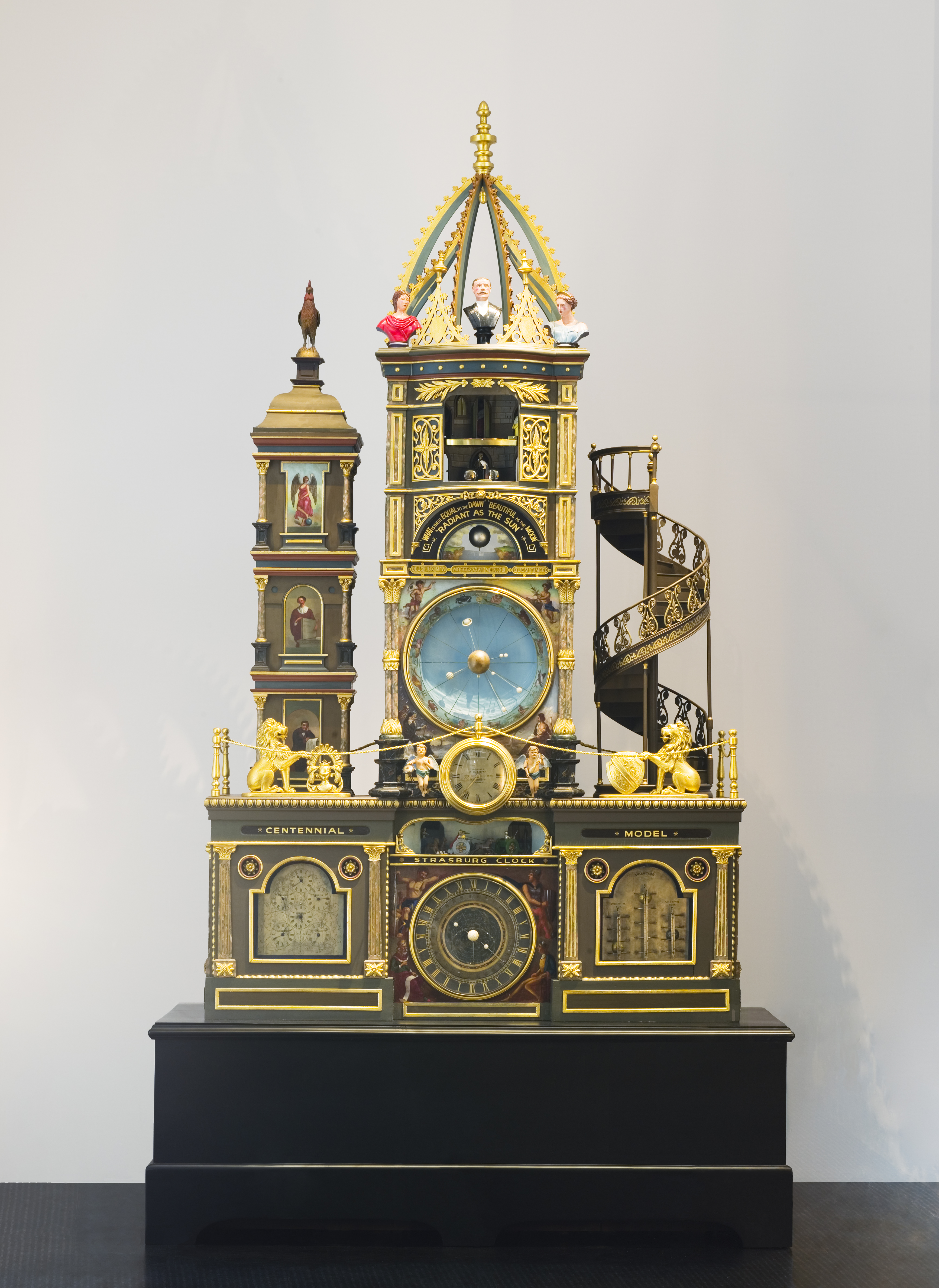 A four-metre high ornate gold clock with a tall centre tower with a procession of the 12 Apostles inside an alcove, a shorter tower on the left and a spiral staircase on the right.