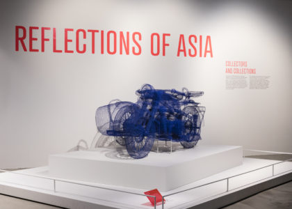 View of an exhibition title 'Reflections of Asia: Collectors and Collection on a white wall and an art work made of blue wire.