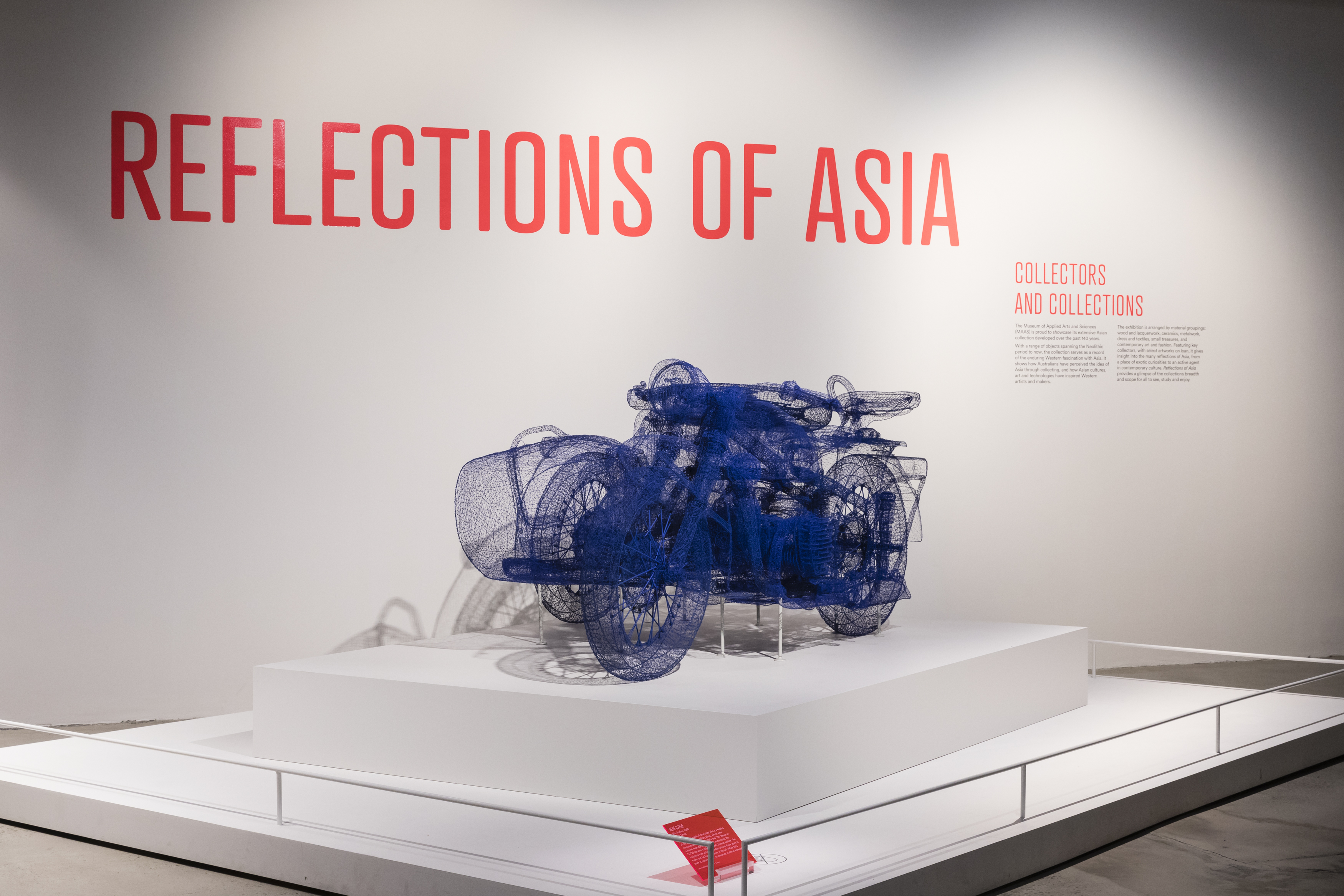 View of an exhibition title 'Reflections of Asia: Collectors and Collection' on a white wall and an art work that is a motorcycle made of blue wire.