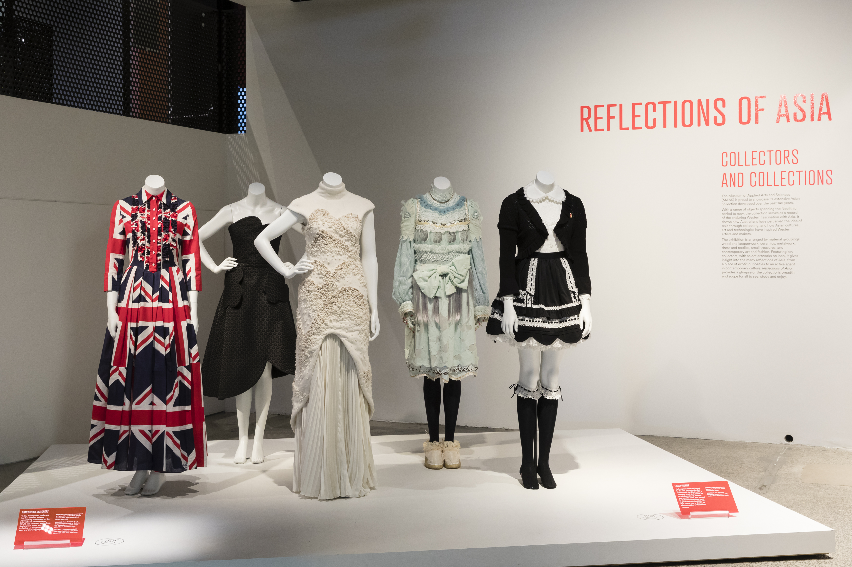 Exhibition view of an open display of contemporary fashion items on five mannequins. There are Victorian style outfits and a dress with Union Jack design.