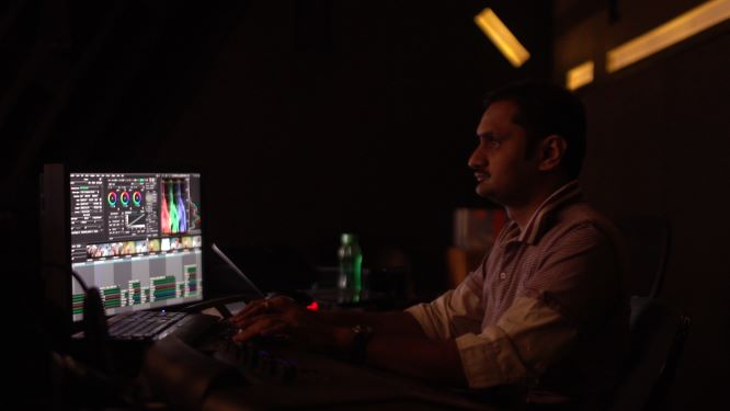 Render worker from Bangalore sitting in a dark cubicle, working at a computer screen which shows colourful imaging software.