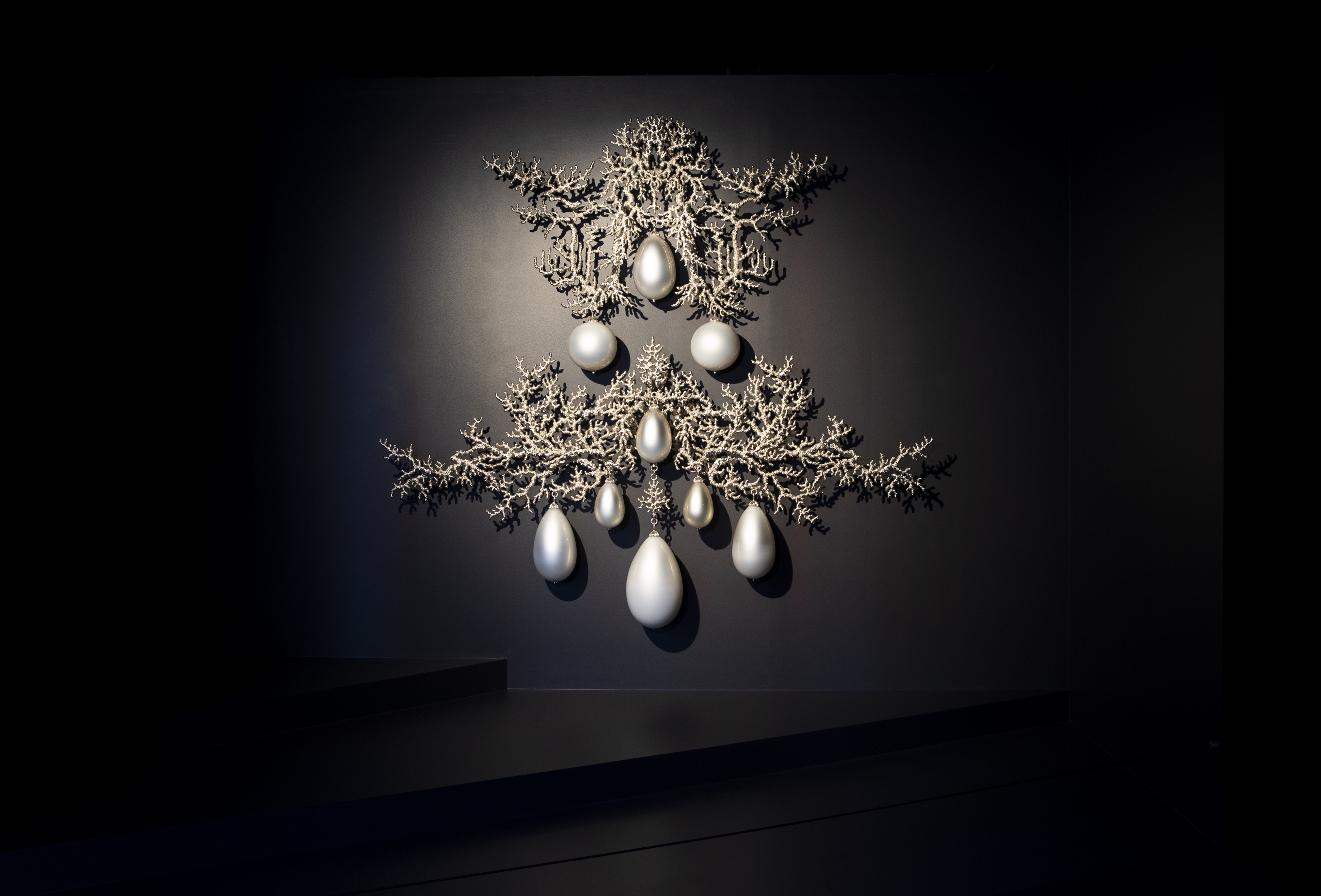 An ornate artwork in silver and white hangs on a black wall. It is in the form of a large symmetrically designed earring formed from silvery coral-like branches set with tear-shaped white glass pendants that look like pearls.
