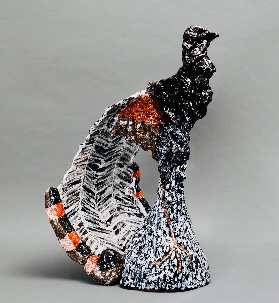 Alt text: Ceramic sculpture of a stylised male lyrebird in black, red, brown and white. The lyrebird stands erect on a mound of earth with its lyre-shaped feathered tail lowered and curved behind it.