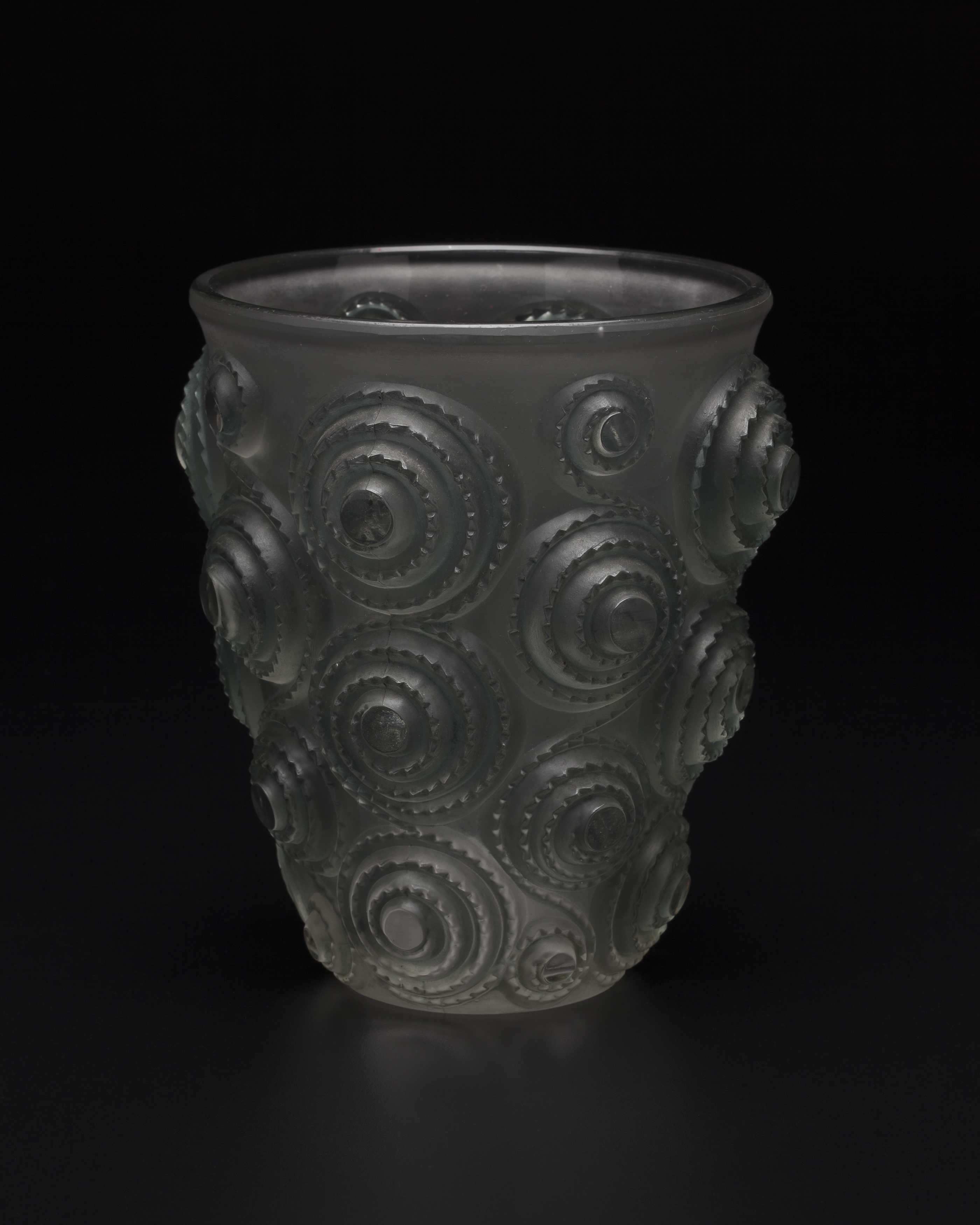 A heavy, cylindrical vase in grey glass with frosted finish, tapering towards the base from a wider rim. The bold, high-relief surface has alternating vertical rows of interlinked notched spiral-shaped forms.