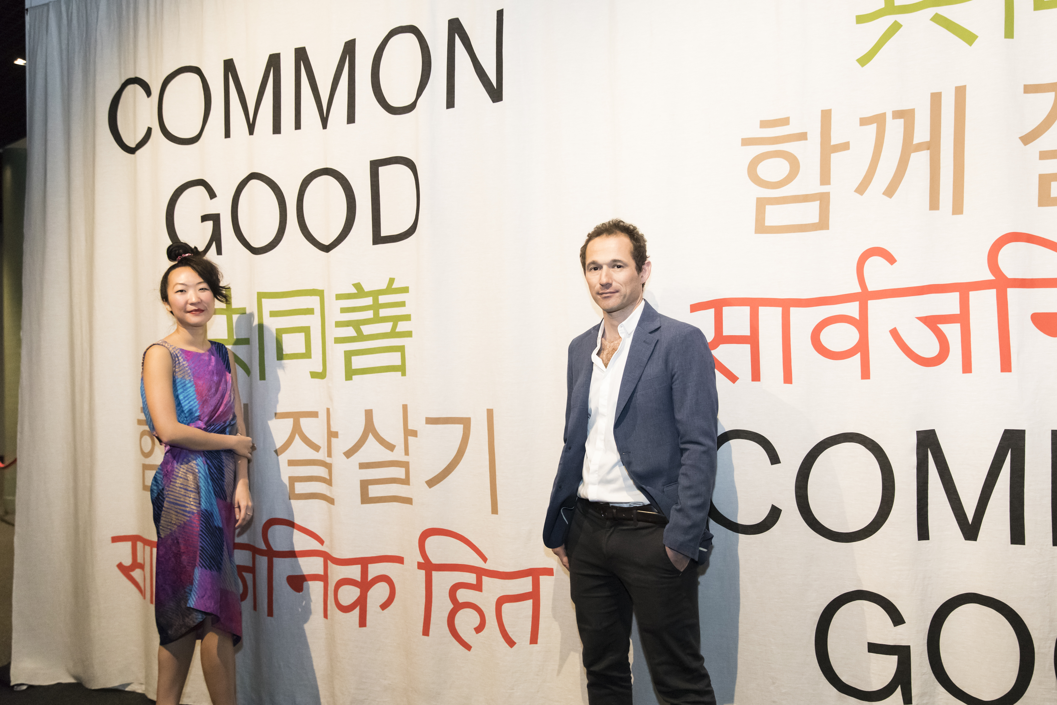 Man and woman posing in front of a curtain with Common Good written on it in various languages.
