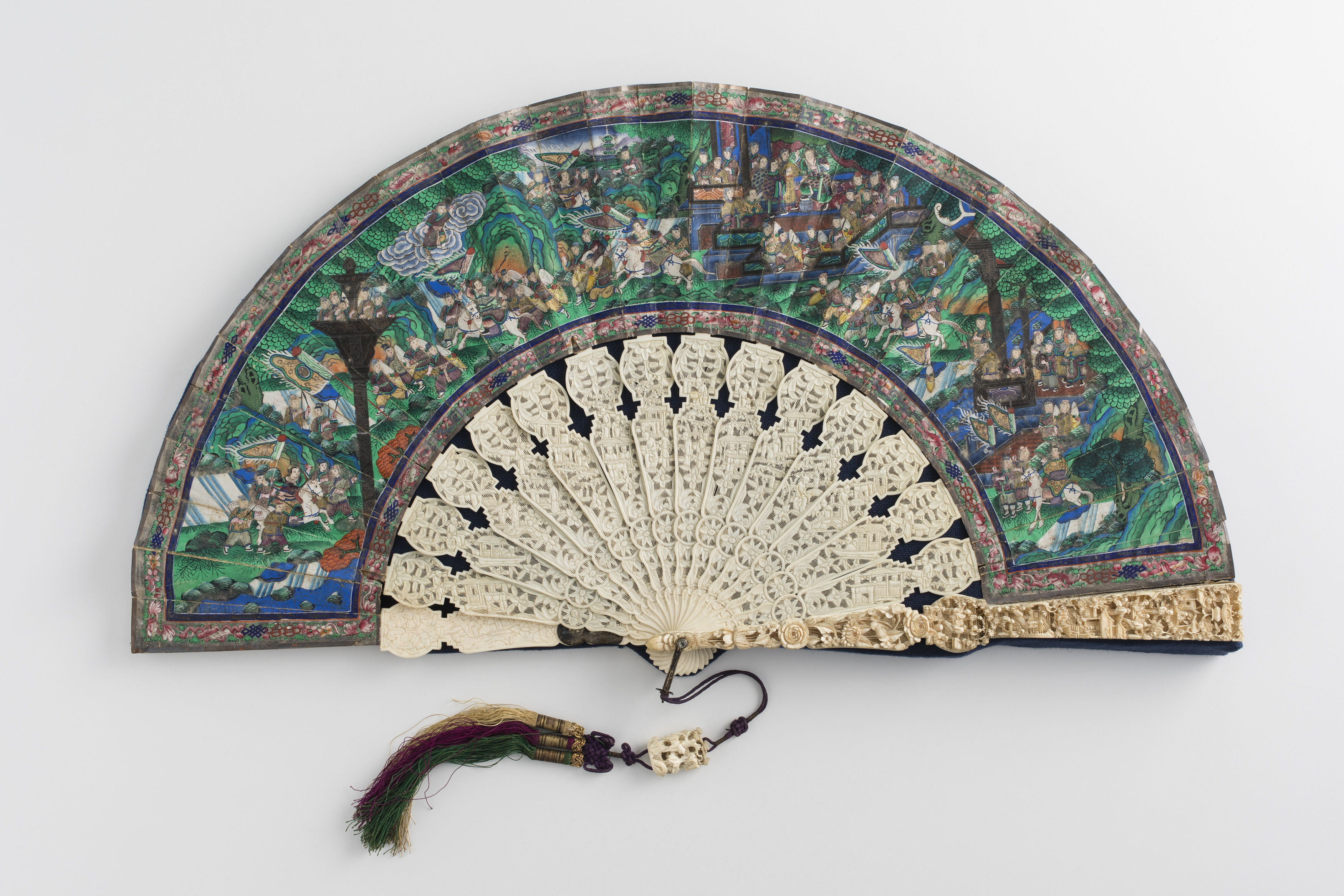 Chinese folding fan open on a grey background. The blades are intricately carved ivory and the painted paper surface (leaves) portrays a busy landscape, depicting what looks like a historic scene with many small brightly coloured figures.