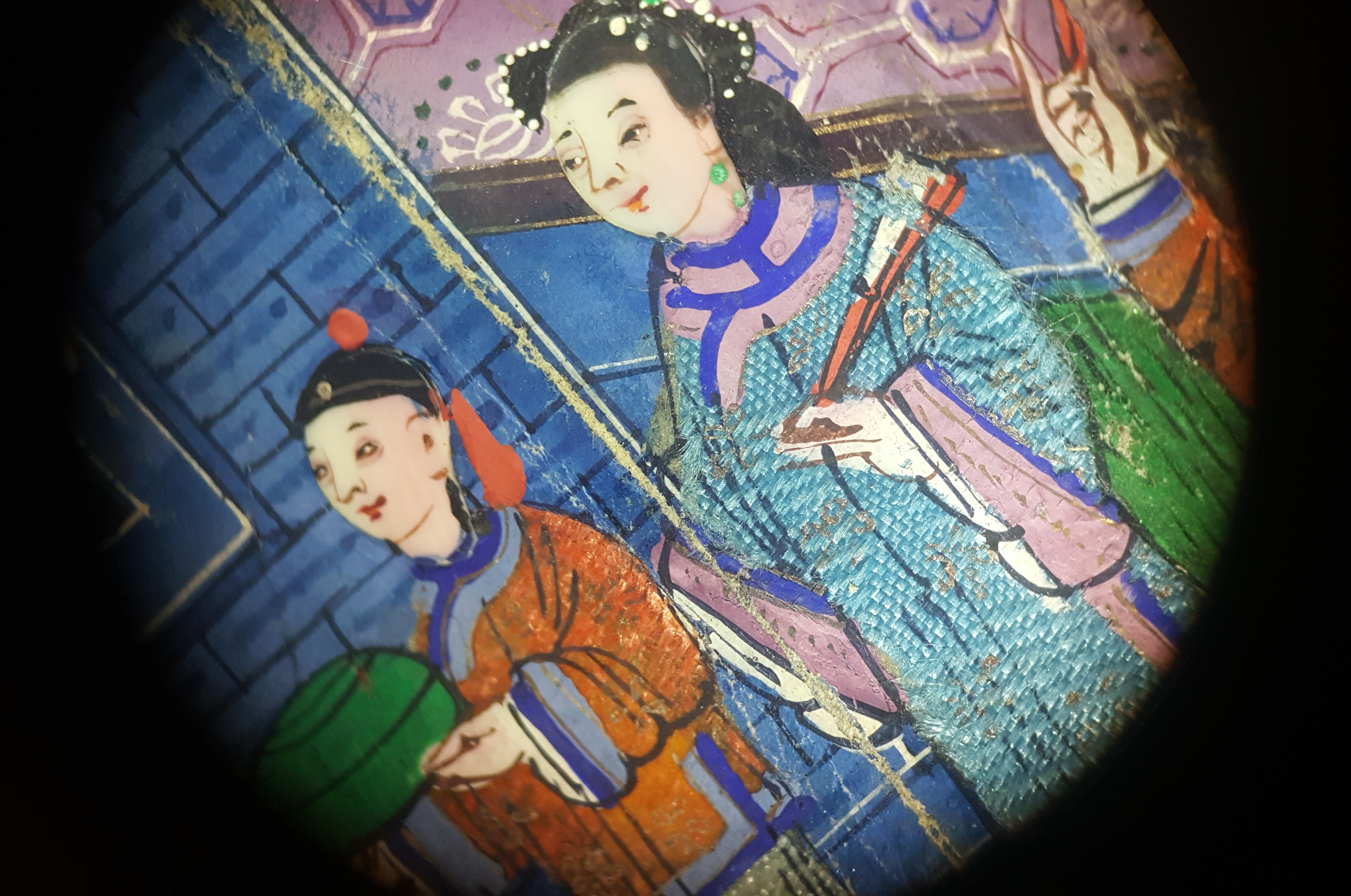 A close detail of two small figures on the fan, of a young man in an orange robe and a woman in a blue robe in front of a blue wall, showing the finely painted woven textile and ivory faces