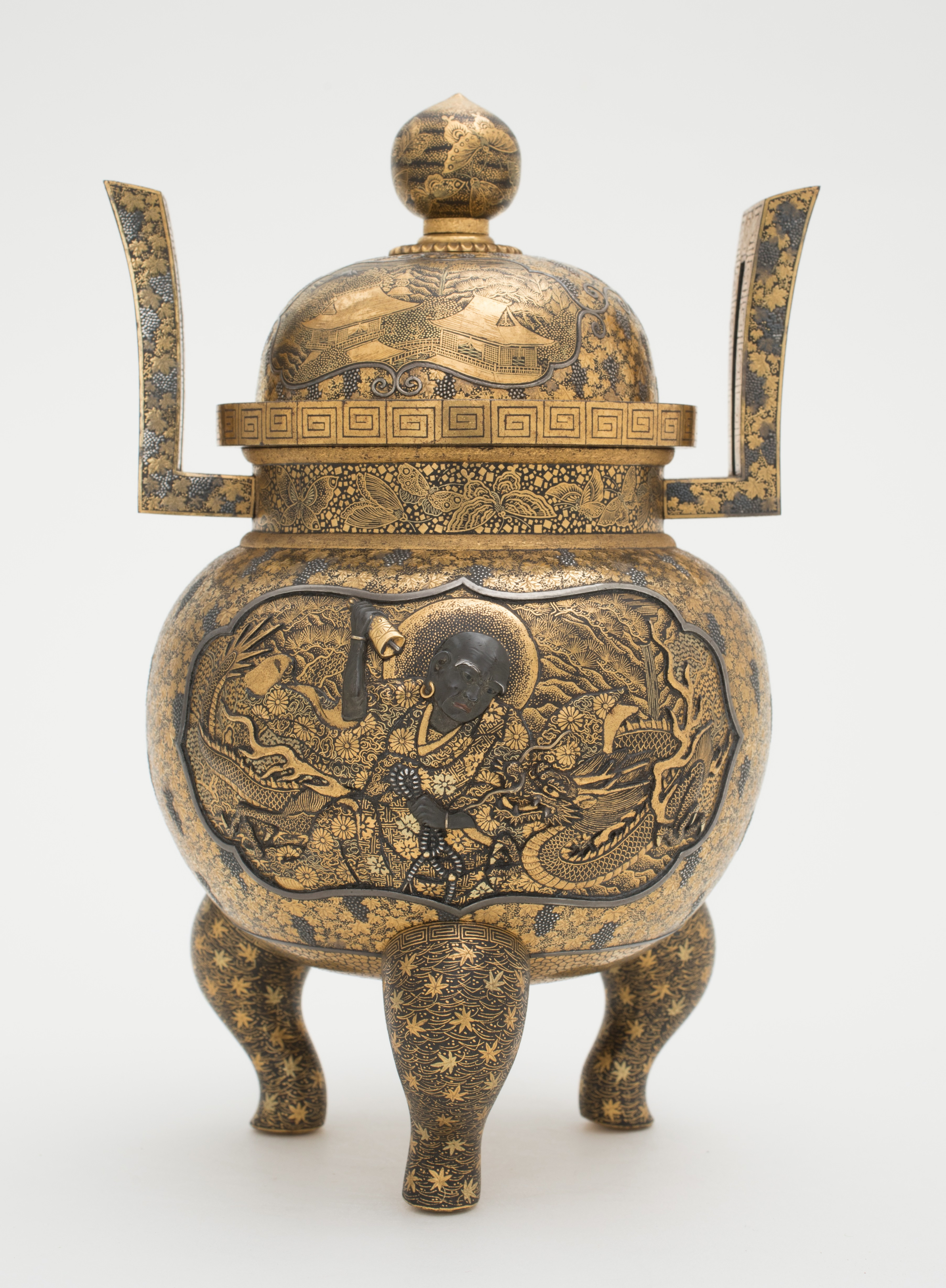 Three legged koro with lid and upright handles on either side. On the belly of the incense burner is a dragon and a budda who is holding a bell in one hand and a string of beads in his other