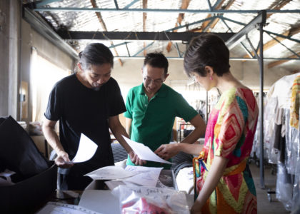 Two men and a woman stand around a table discussing fashion drawings and fabric samples. They are in the designer's studio with garments hanging on racks in the background.
