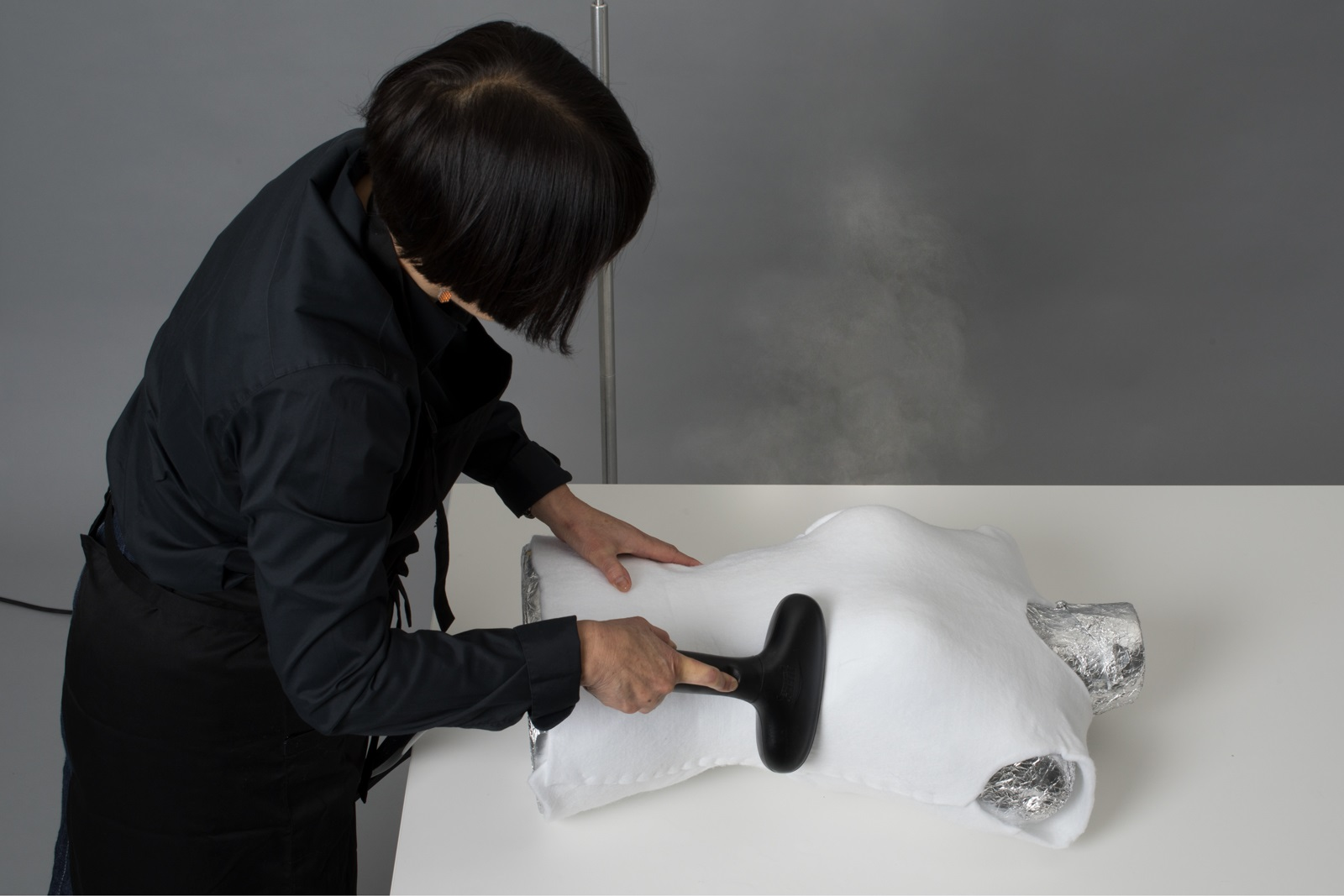 A woman works on a dress form lying on the table in front of her. The dress form is covered in aluminium foil over which Suzanne is steam-moulding a synthetic white felt in order to create a stylised body shape.