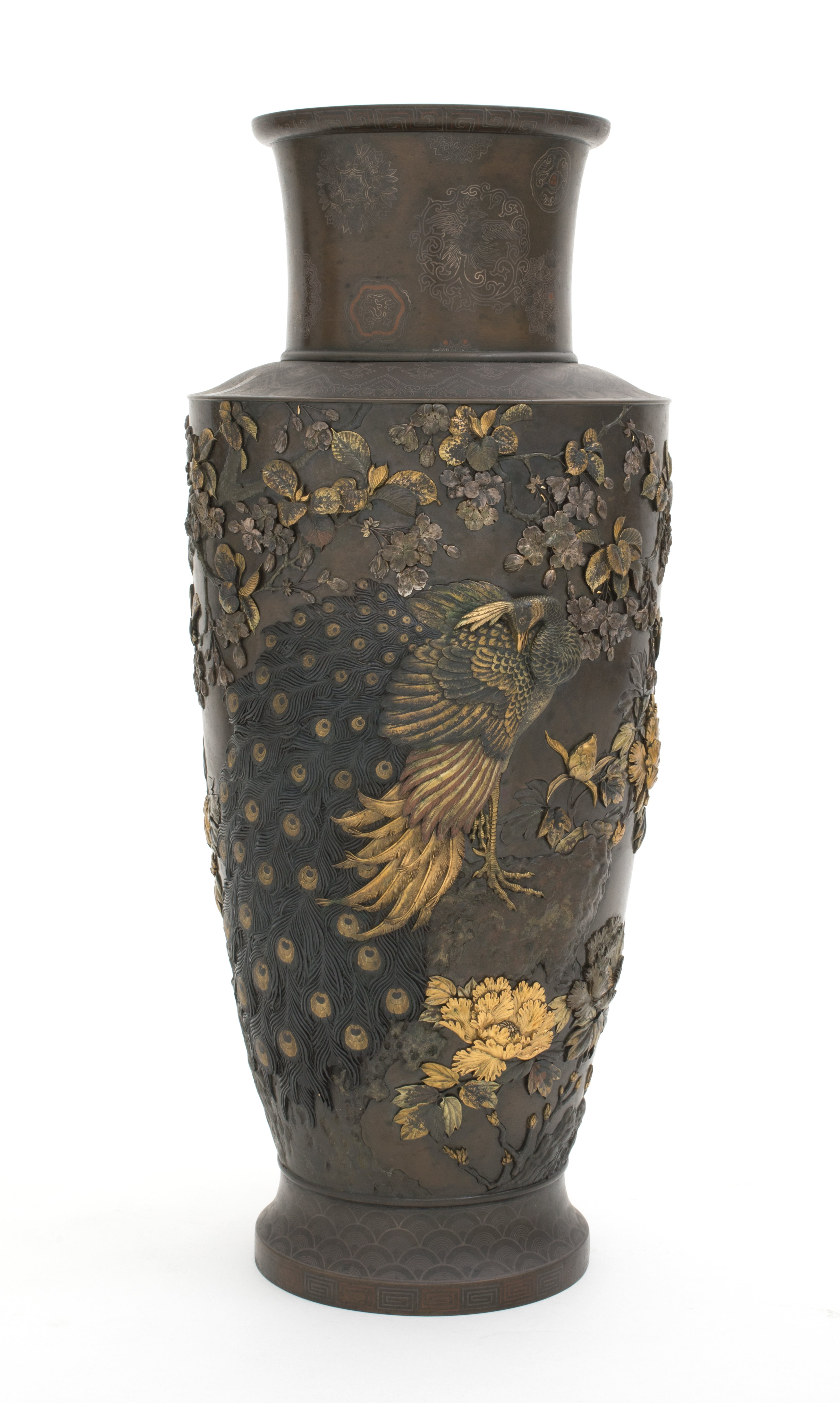 Bronze vase with a single peacock in the centre with foliage and pink tinged blossoms overhead and the golden peony underneath.