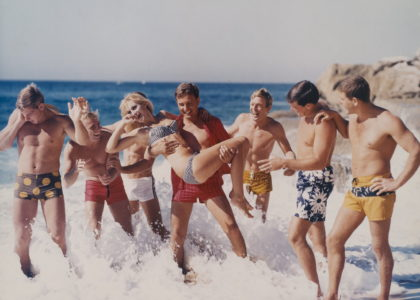 A staged colour photograph taken in the 1970s for advertising featuring seven young men wearing board shorts. The man in the centre is holding a young woman with blond hair and wearing a bikini.