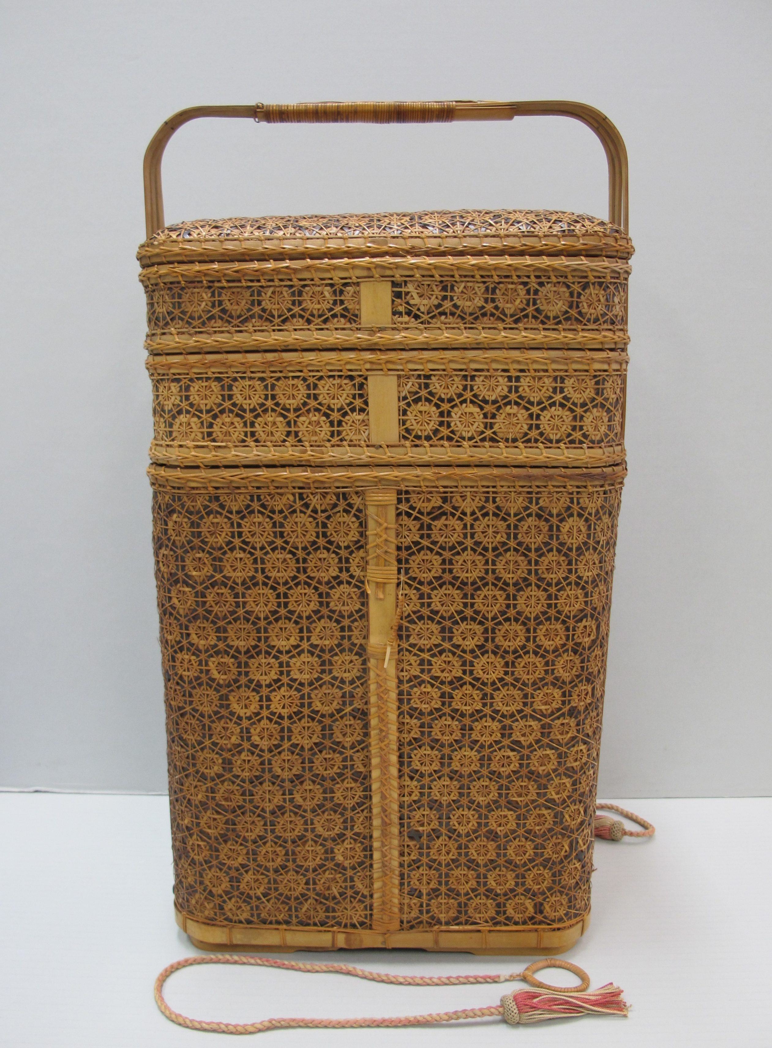 Intricately woven bamboo basket with three tiered compartments, a lid, handle and two silk ties with tasseled ends.