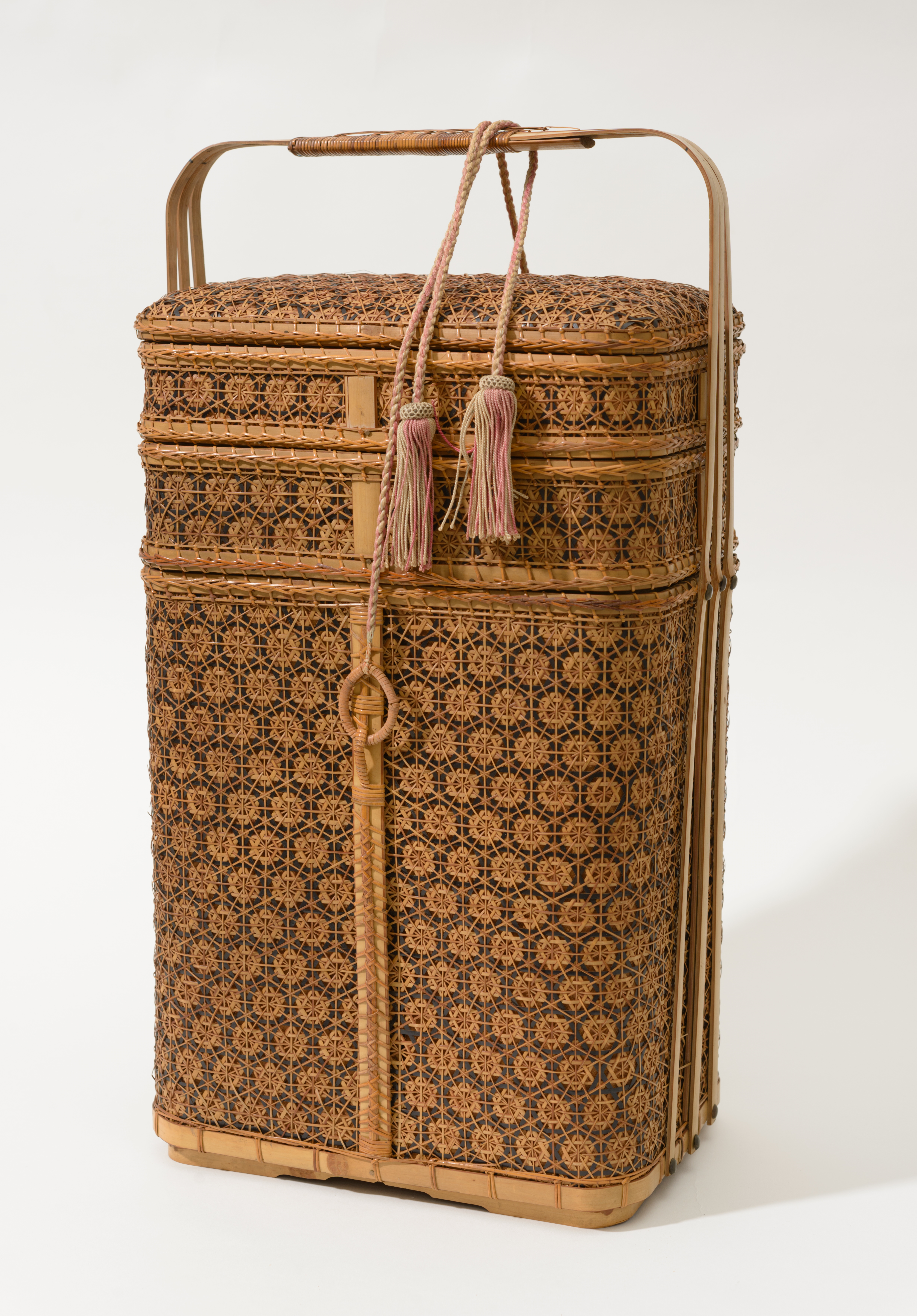 Three-tiered woven bamboo basket, with the silk tie reinstated to the repaired attachment loop. The tassel ties have been displayed looped and draped around the single handle which extends from the sides over the top of the basket.