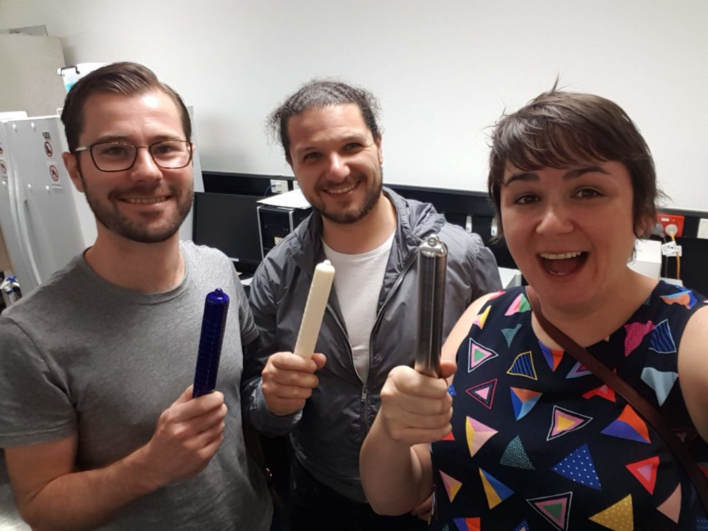 Three scientists holding condom forming prototypes: two 3D plastic printed and one metal.