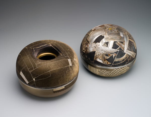 Covered rice bowl, male bowl, one of pair. The male rice bowl has a domed lid, and both the lid and bowl are densely covered in intricate patterns, using gold, silver and odong (a copper-gold alloy, similar to Japanese shakudo) inlaid wire, with a blue-black oxidised steel background. The inlaid patterns are inspired by Korean Joseon dynasty bojagi (wrapping cloths). Covered rice bowl, female bowl, one of pair. The female rice bowl has a hole in the centre of its lid, and is decorated with silver, gold and bronze inlaid wire against a blue-black oxidised steel background. The inlaid patterns are inspired by Korean Joseon dynasty bojagi (wrapping cloths) and the chisel marks covering the surface give the appearance of fabric.