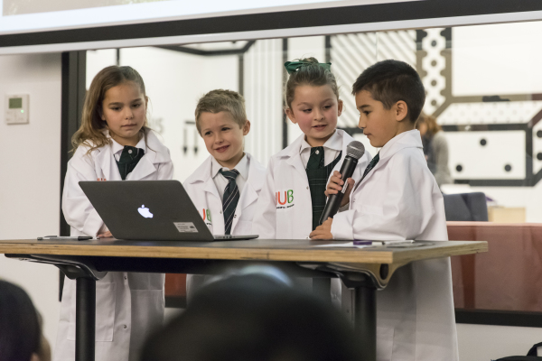 Group of children wearing white lab coats standing at a desk with a computer. One is speaking into a microphone.