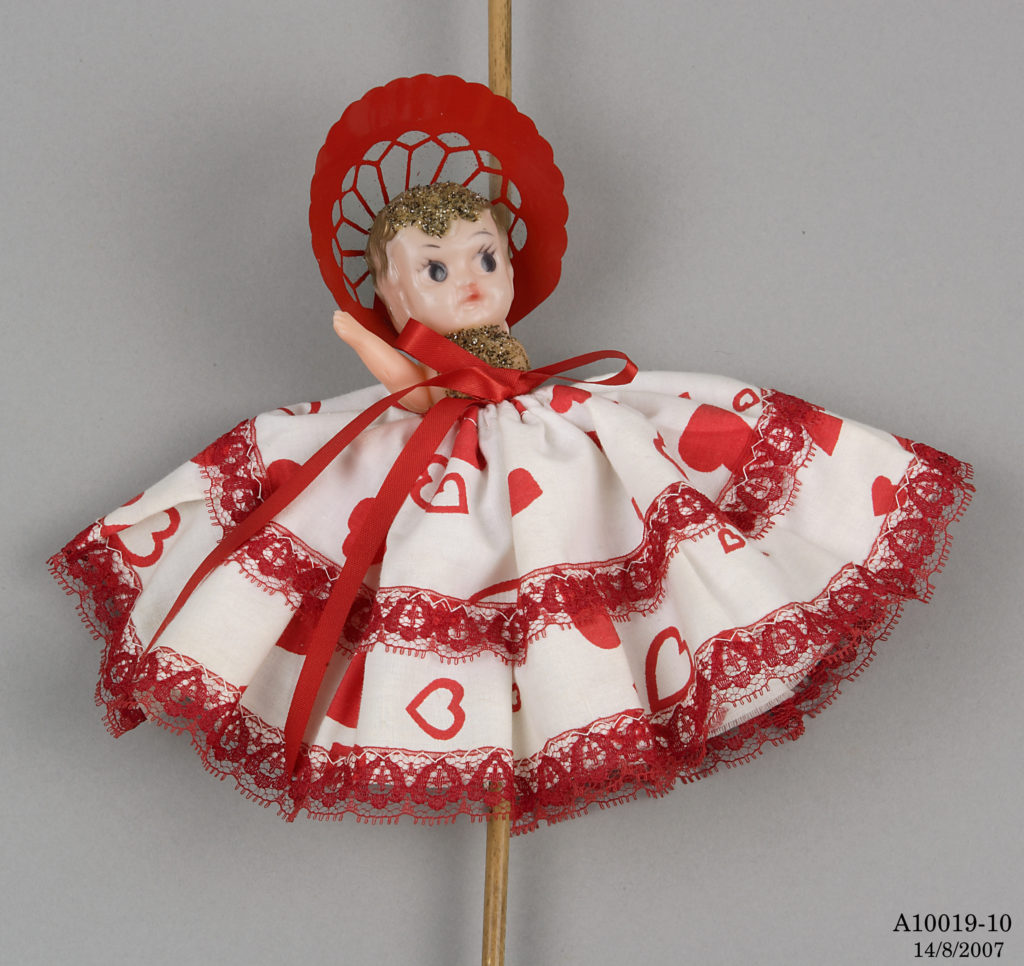 Small plastic doll with gold painted hair wearing a red bonnet and a sequin top. She is dressed in a full skirt made of white fabric decorated with red hearts and red lace and ribbons. The doll is attached to a cane walking stick.