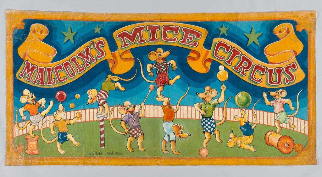 A painted banner with blue background and yellow border depicting numerous cartoon style mice dressed in shirts and tops, performing acrobatic acts in a circus ring.