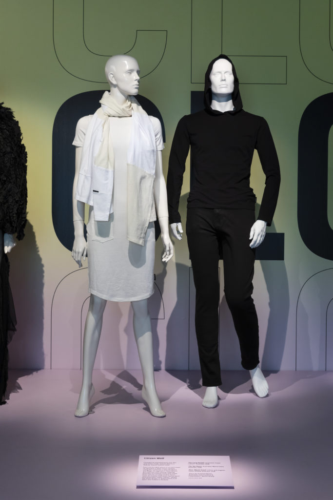 Citizen Wolf clothing on display - white dress and scarf on female mannequin, black hoodie on male mannequin