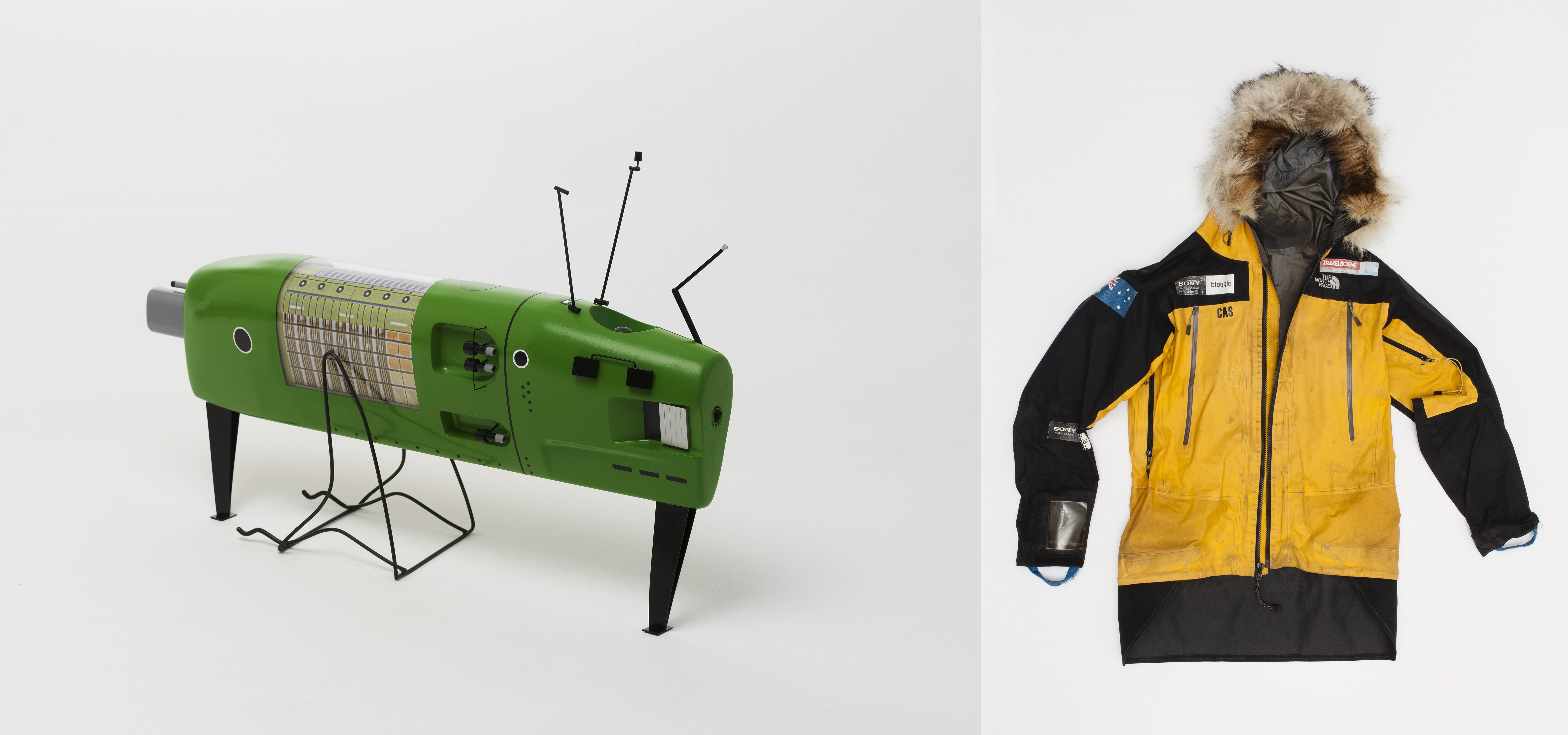 Two images side by side. Left: Model of a green submarine. There are various panels and instruments on the exterior of the vehicle. Right: Black and yellow weatherproof jacket with fur around the hood. There is an Australian flag on one sleeve and the name 'CAS' written on the chest.