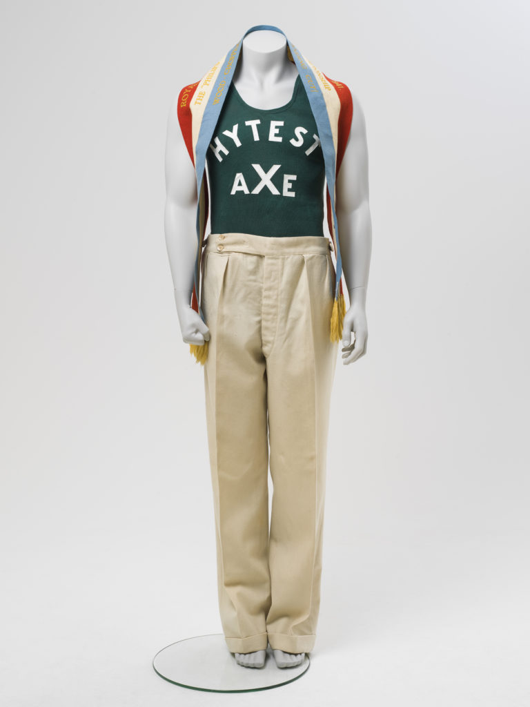 Mannequin wearing a green-coloured cotton ribbed 'Chesty' Bonds Athletic singlet with 'HYTEST AXE' in white vinyl lettering on the front and back, and cream trousers. Around his neck is a championship ribbon for wood chopping.