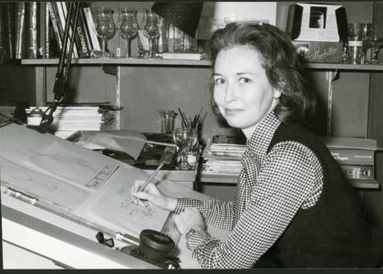 Black and white photograph of a woman working at a drawing board.