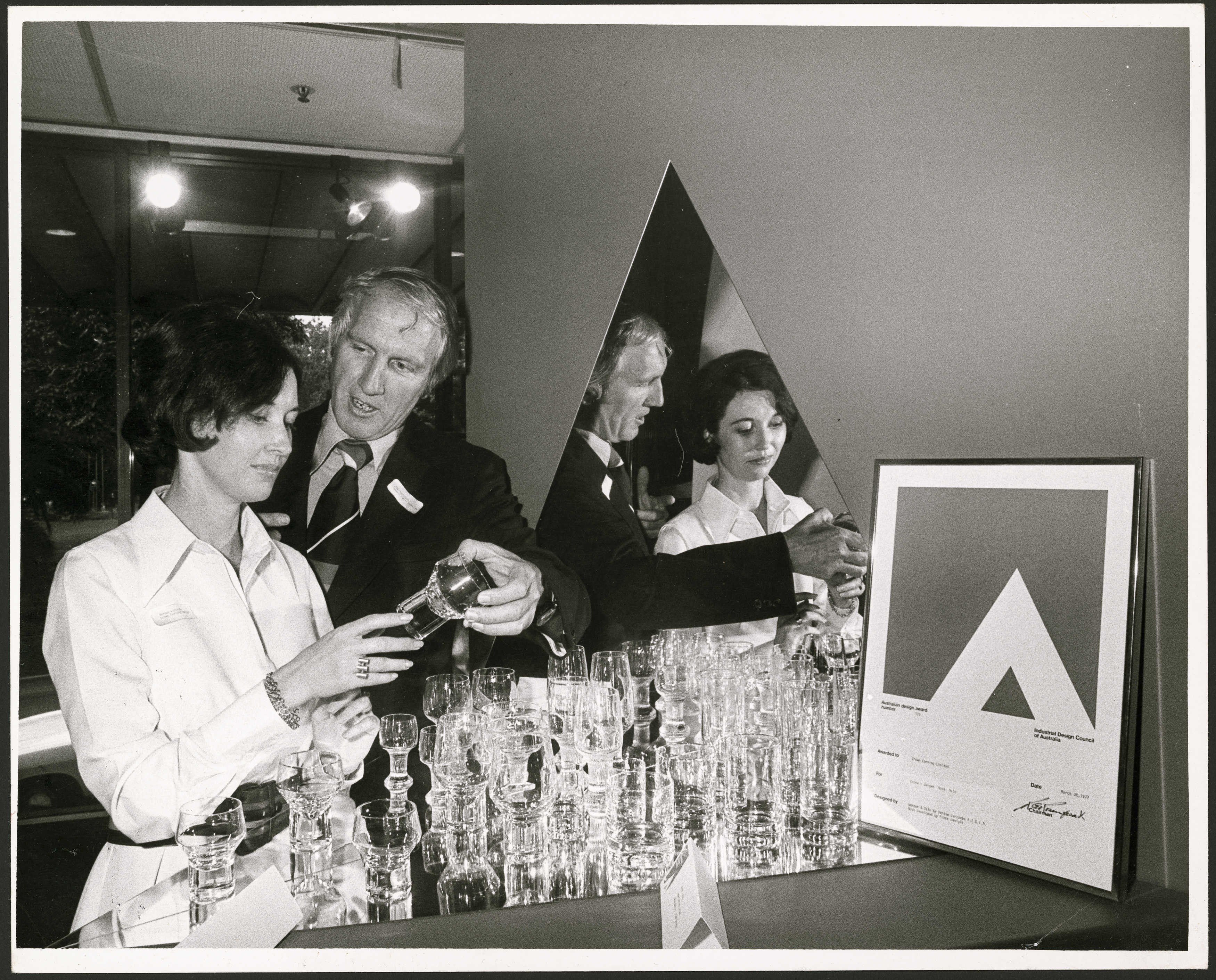 Black and white photograph of a woman and man, both holding a drinking glass. There is a large display of drinking glasses in front of them and a framed award on the right of the image.