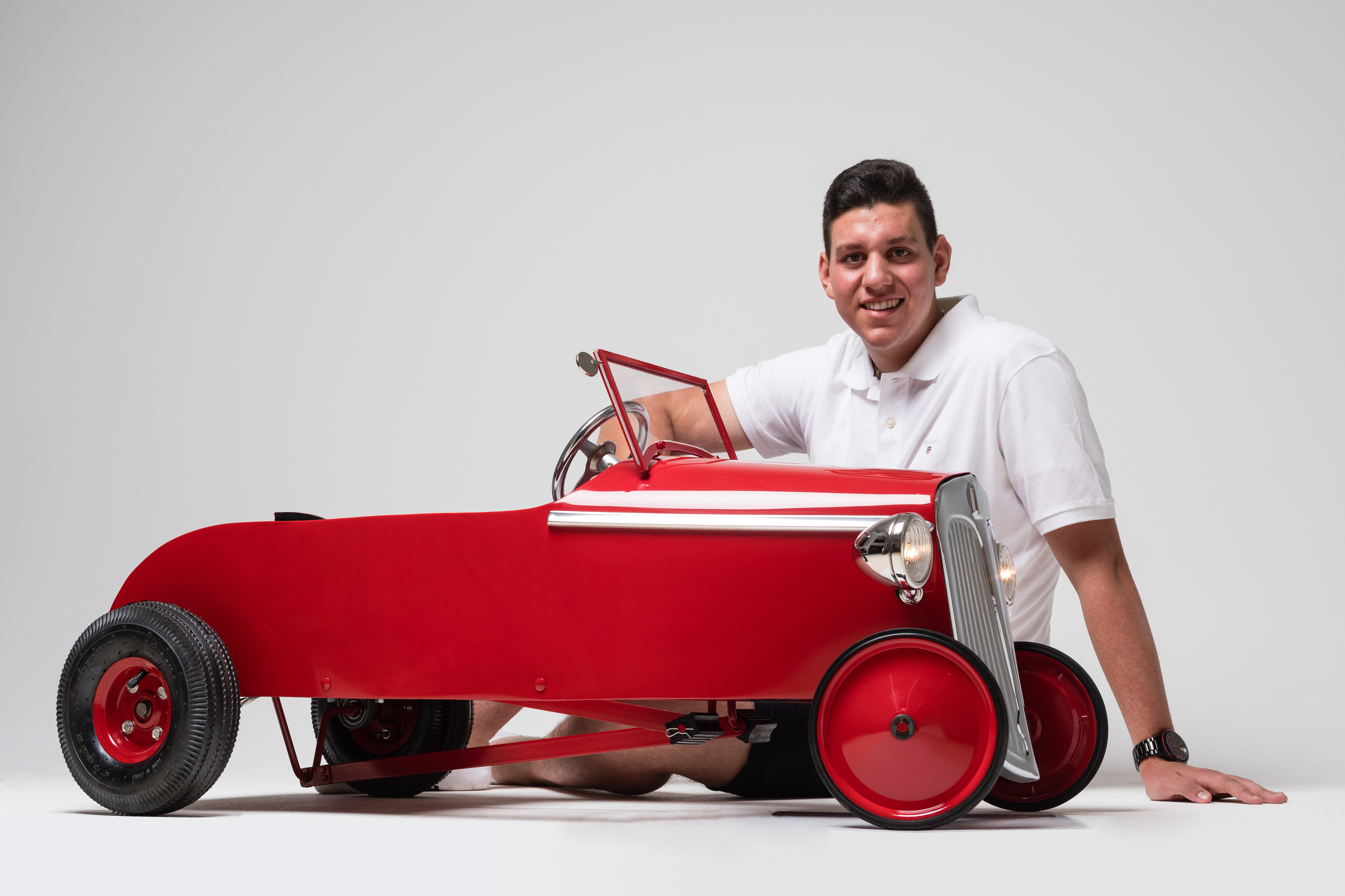 A young man sitting on the floor behind a small, bright red pedal car.