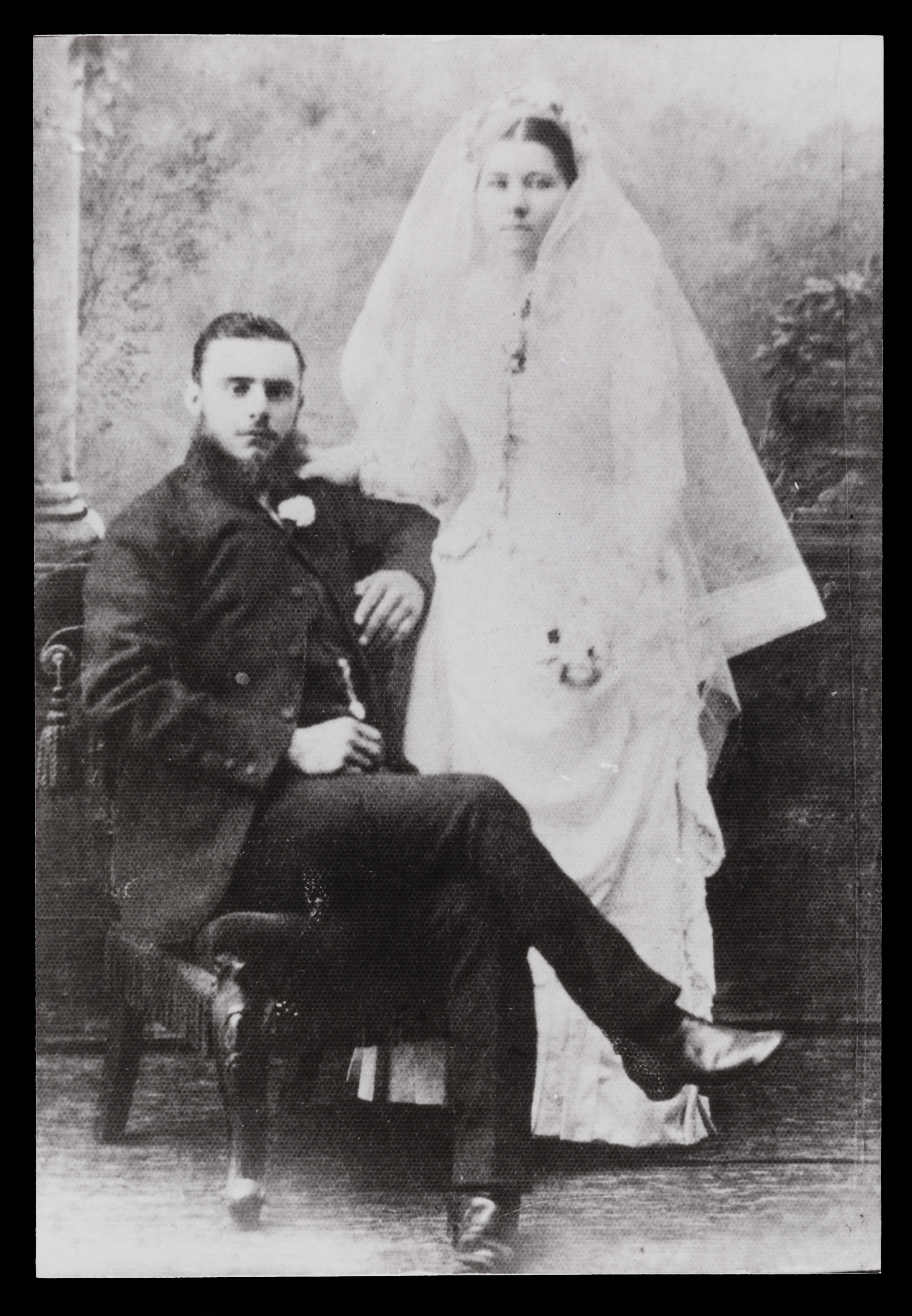 Black and white wedding photograph. The groom is wearing a suit and sitting in a chair, and beside him stands the bride in a white wedding dress and veil.