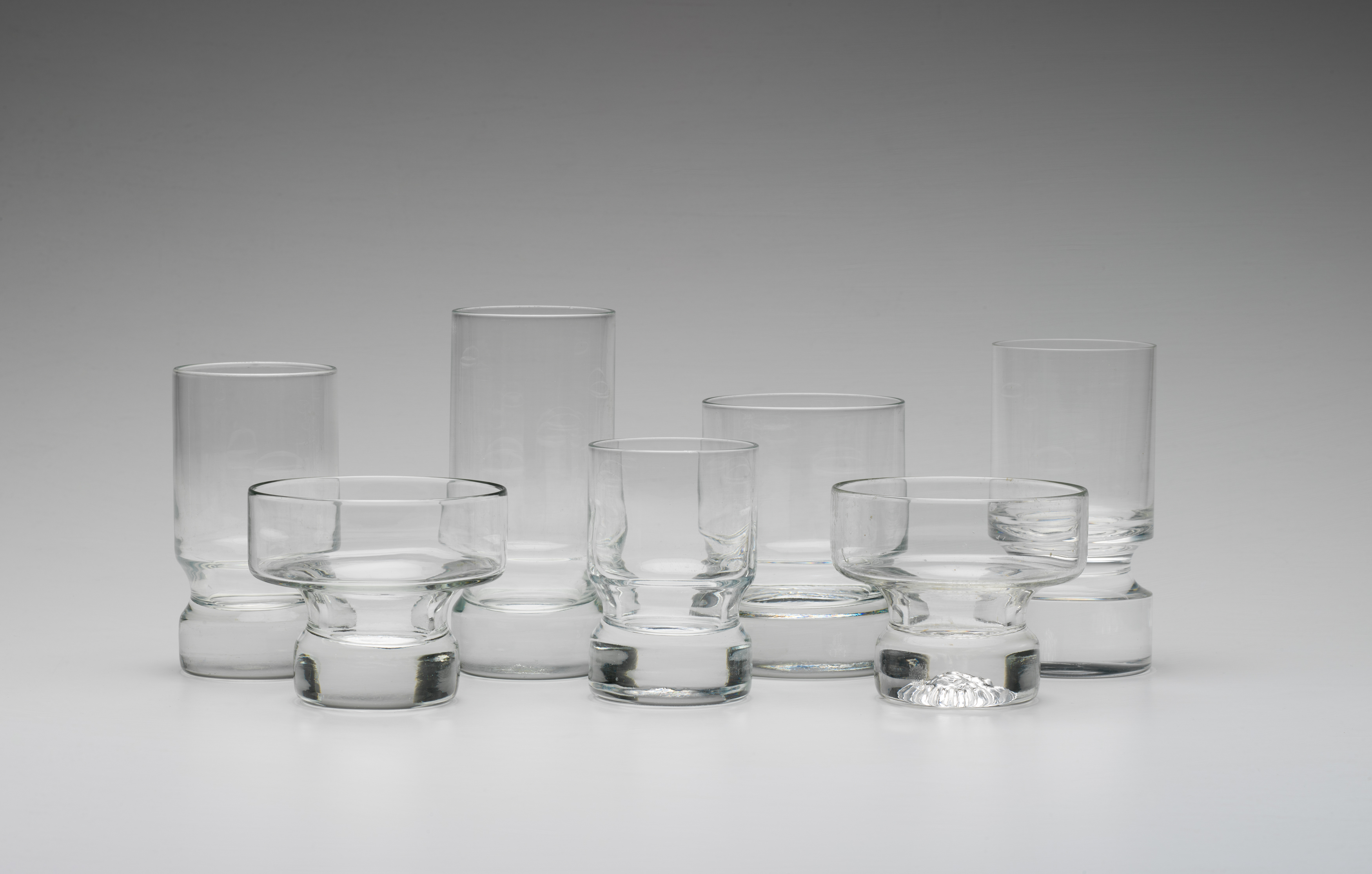 Seven drinking glasses of different shapes and sizes on a grey background.