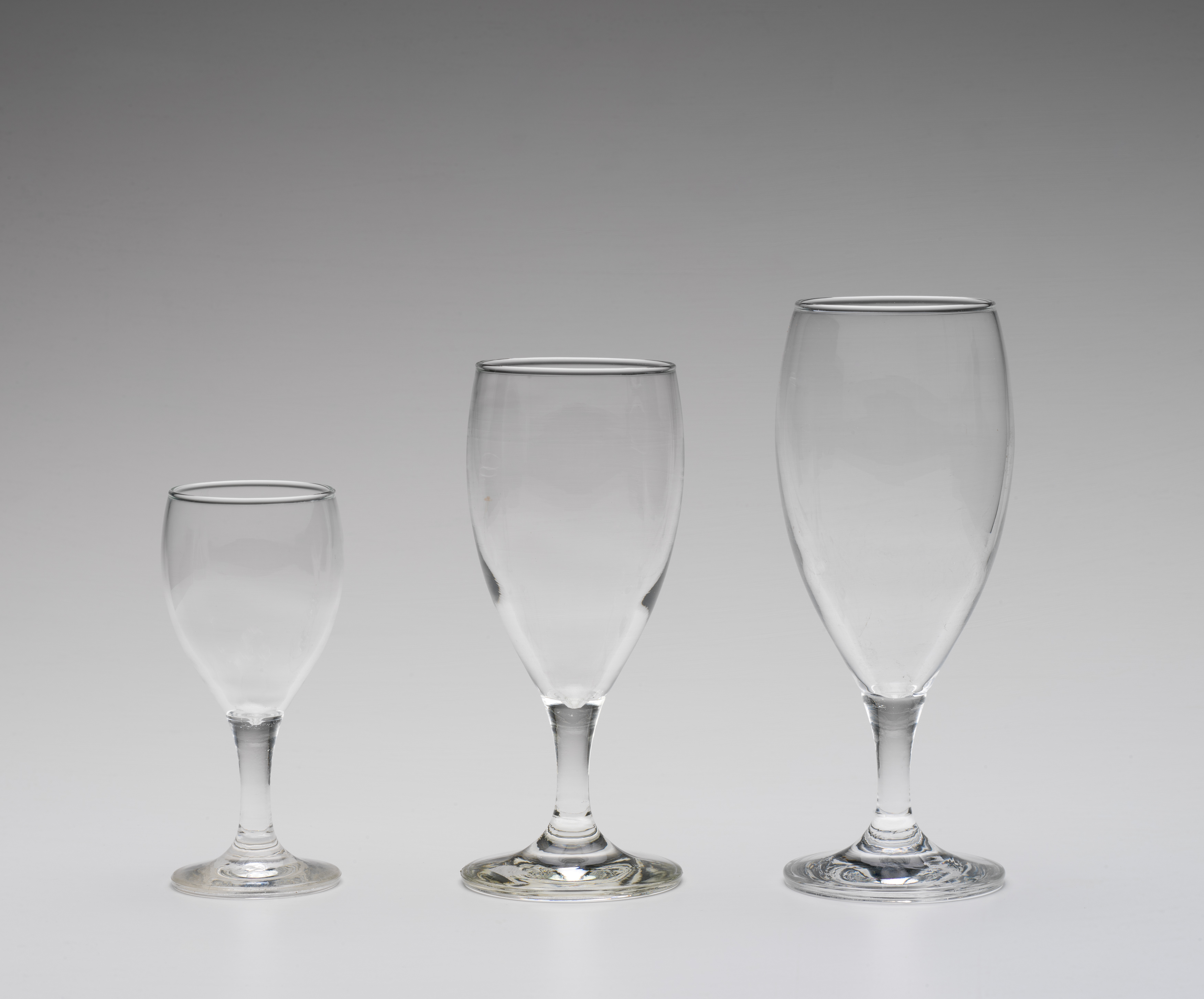 Three wine glasses of different sizes on a grey background.