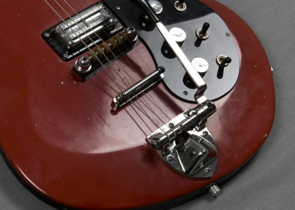 Electric guitar, 'Astro-Jet' with case and guarantee. Assymmetrical double cutaway solid timber body finished in crimson with bevelled edges; rosewood fingerboard; two pickups (treble and bass) and three control knobs for tone and volume; four machineheads on bass side and two on treble side of headstock.