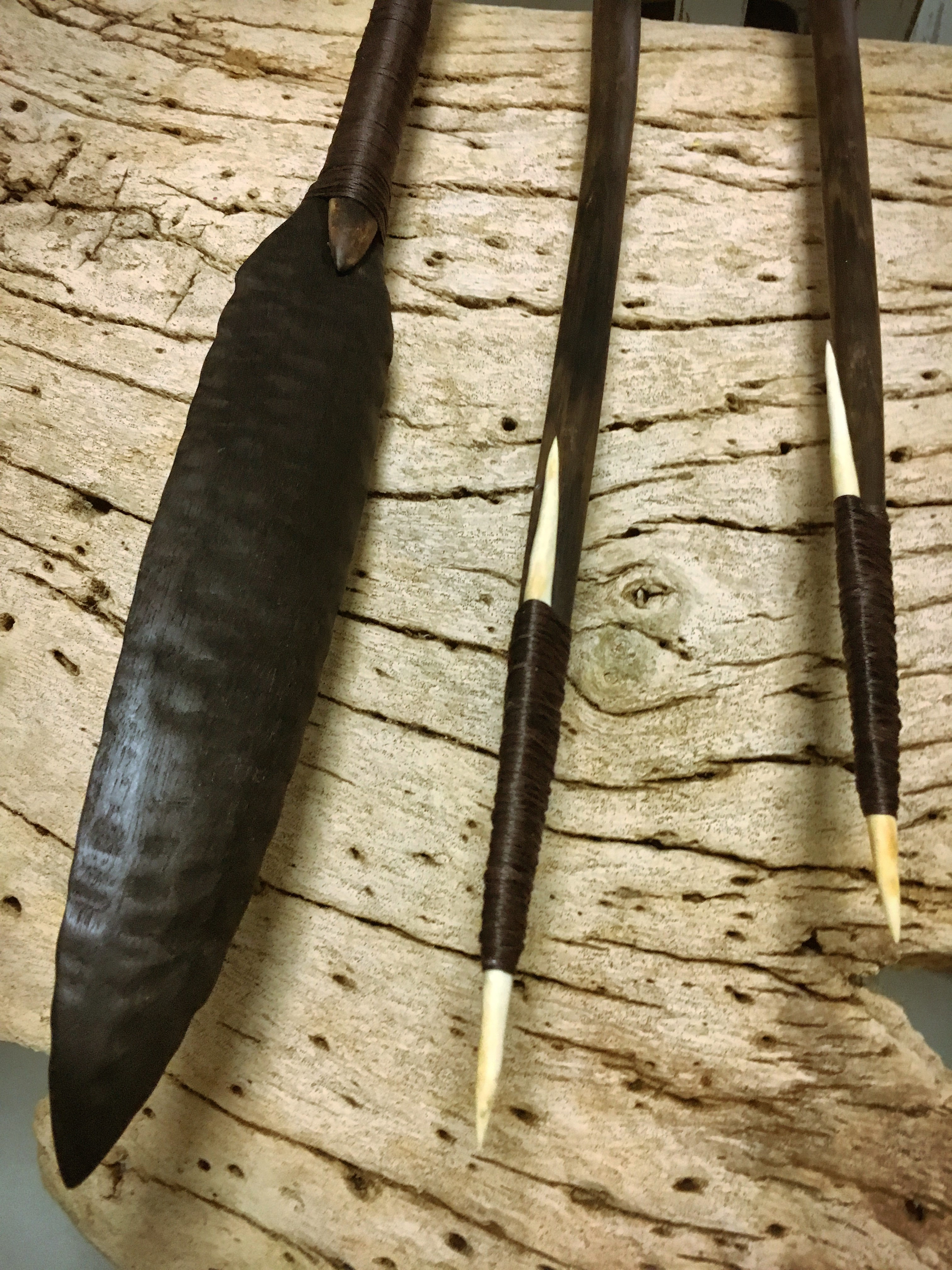 the tips of three spears rest on a smoothed out wooden plank, the left most spear is tipped with a flat broad head the two right most spears are tipped with a thin fine bone head.