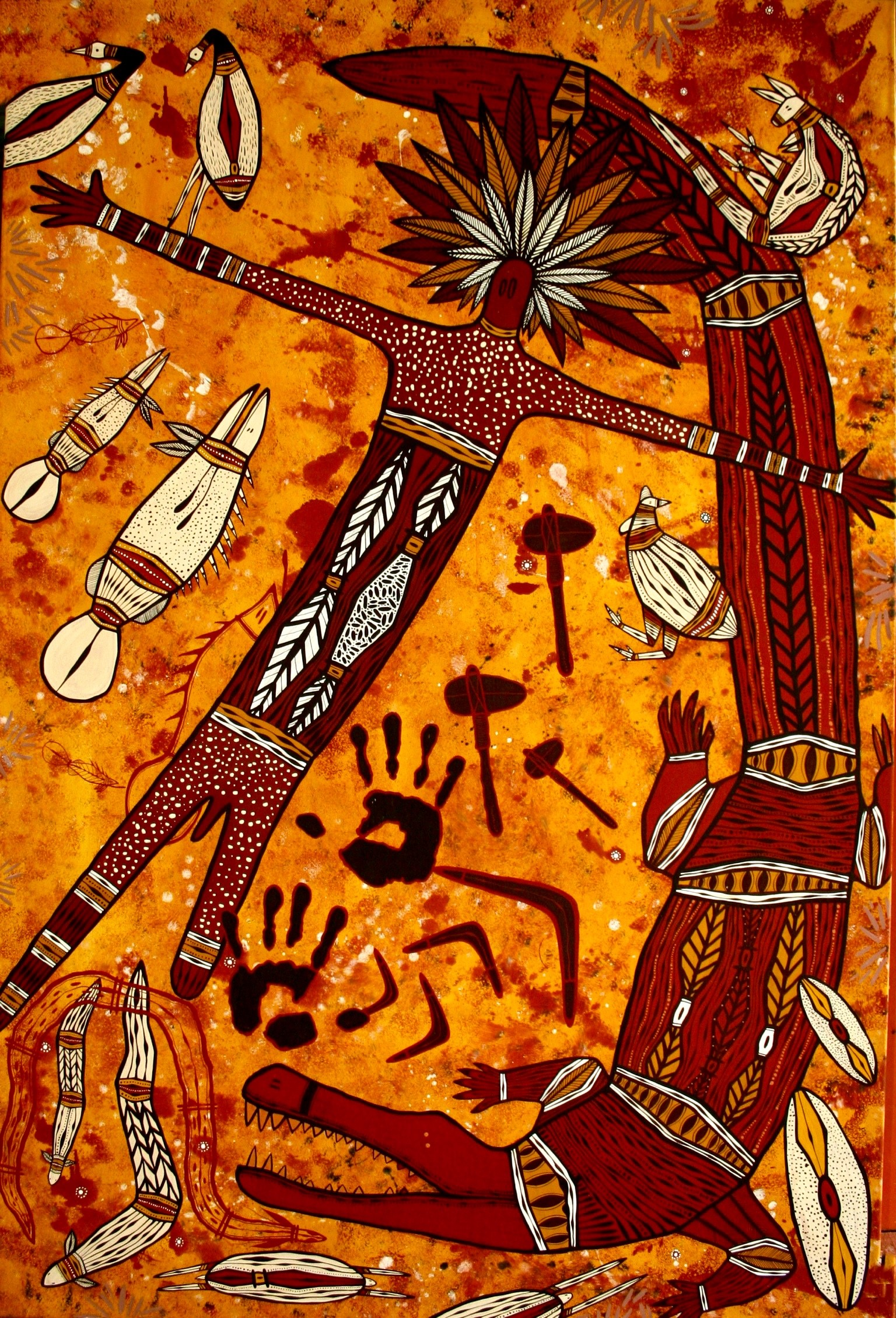 indigenous painting depicting a male figure with headdress and crocodile. Colours are red, black, orange and white. Around the male figure and crocodile the image depicts smaller Australian animals, axes, hand prints and boomerang.