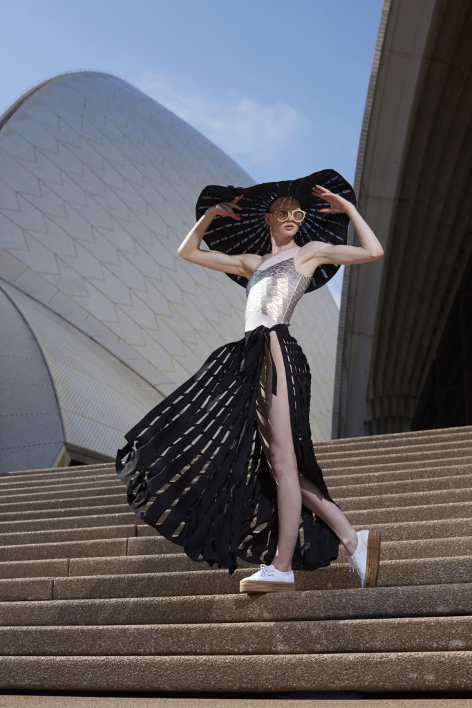 Woman standing on the steps of the Sydney Opera House wearing sunglasses and a large brimmed hat which she holds off her face with both hands.