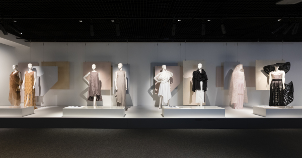 Eight female mannequins dressed in garments designed and made by the four students profiled in Student Fashion 2019. The mannequins are grouped in pairs, and stand in a straight line atop a long rectangular exhibition plinth. Four low rectangular showcases are positioned in front of the mannequins, containing creative process material.