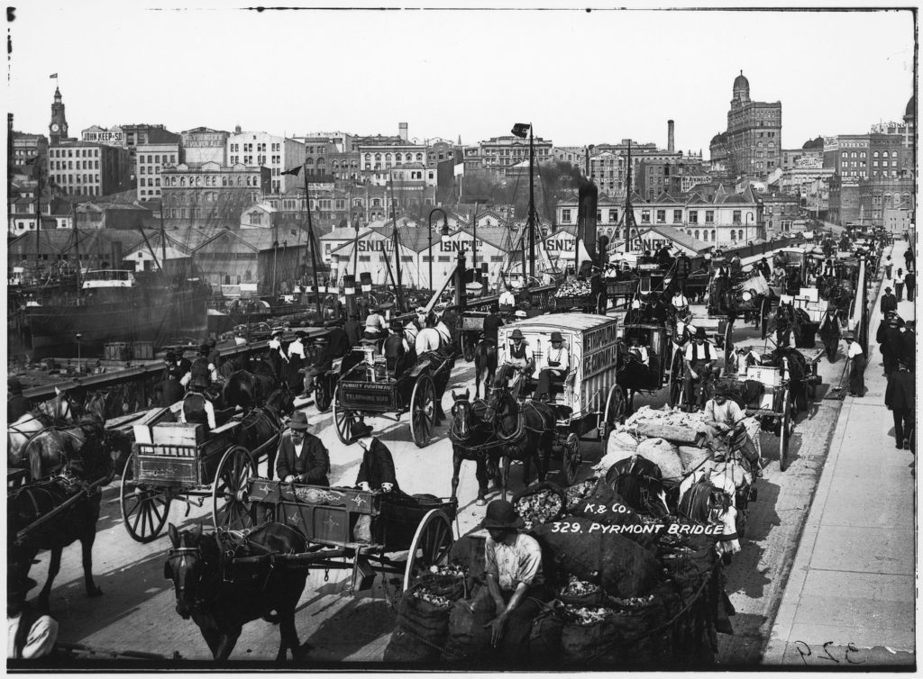 Black and white photo of a bridge filled with horse and carts and pedestrians