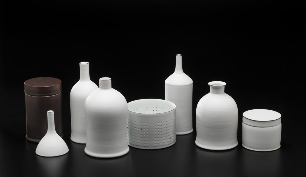 A row of eight small bottles and containers, all in white porcelain except one brown cylindrical box on far left. All photographed against black background.